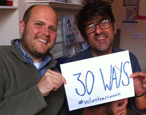 Two men hold a piece of card reading '30 Ways. #volunteersweek'.